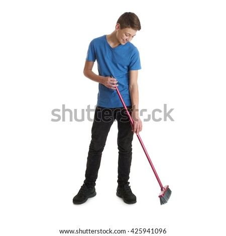 Cute teenager boy in blue T-shirt with broom standing over white isolated background full body  cleaning concept