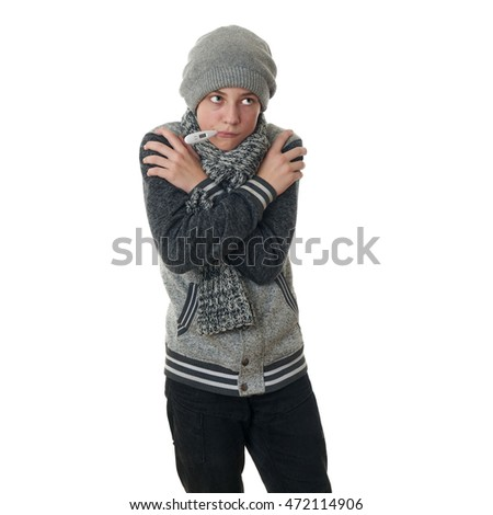 Cute teenager boy in gray sweater, hat and scarf with thermometer in mouth and crossed arms over white isolated background, half body