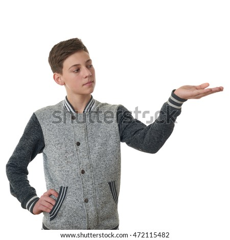 Cute teenager boy in gray sweater presenting something on hand over white isolated background, half body