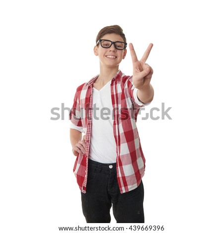 Cute teenager boy in red checkered shirt and glasses showing victory over white isolated background, half body - stock photo