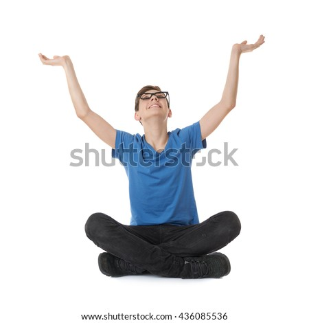 Cute teenager boy stretching hands up  in blue T-shirt, glasses and lotus posture over white isolated background - stock photo