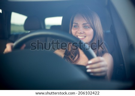 Cute teenager driving her brand new car - stock photo