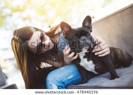 Cute teenager girl enjoying outdoors in cafe bar together with her adorable French bulldog puppy. Strong back light. Warm sunny day.