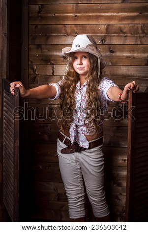 Cute teenager girl in a cowboy hat on a ranch posing in studio - stock photo