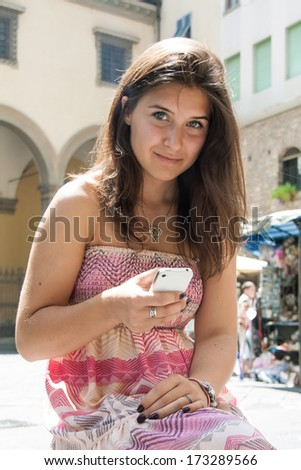 Cute  teenager girl with  mobile phone in the city summer