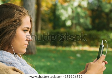 Cute Teenager Listening to Music on a Cell Phone in the Park - stock photo