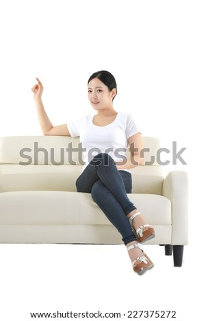 Cute teenager sitting on a sofa isolated on white background