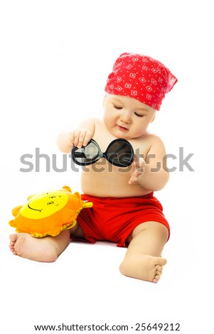 cute ten months old baby wearing summer clothes putting on sunglasses - stock photo