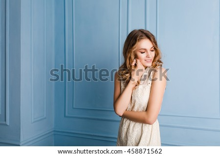 Cute tender slim girl with blond curly hair standing in a studio with blue background. She smiles and looks sweet. She has arms crossed on her chest. - stock photo
