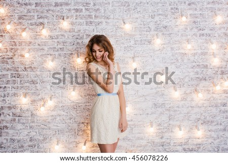 Cute tender slim girl with blond curly hair standing in a studio with white background with flashlights. She smiles and looks sweet. She has her arm near chin. - stock photo