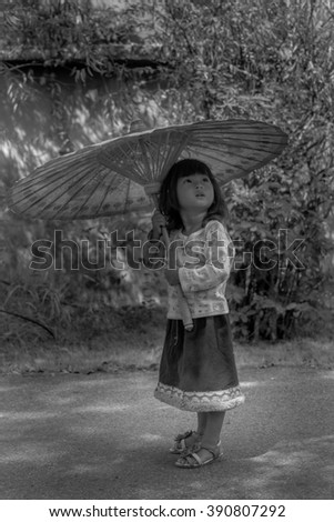 Cute Thai kid holding a parasol and looking upwards, bright future concept. Taken in Black and white.