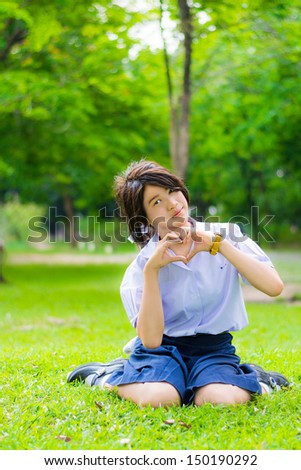 Cute Thai schoolgirl is sitting on the grass and doing heart symbol, spreading love to everyone. - stock photo