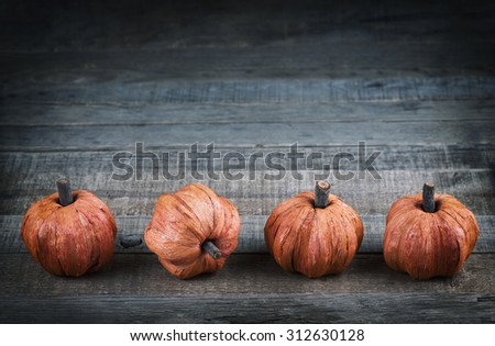 Cute Thanksgiving Mini Pumpkins made of fibers in row at bottom of rustic wood board background with room or space for copy, text, your words. Horizontal dark, cool cross balance tones with vignette