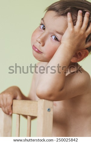 Cute Thinking Caucasian Little Boy Sitting On Chair. Vertical Image Composition - stock photo