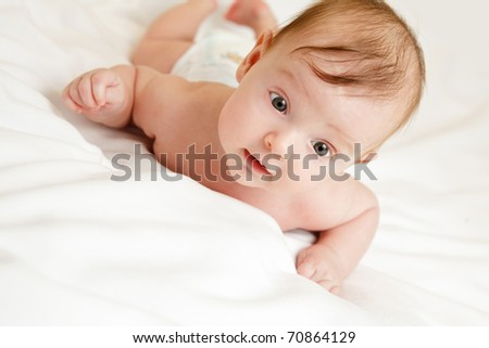 Cute three months old caucasian baby girl on white blanket.