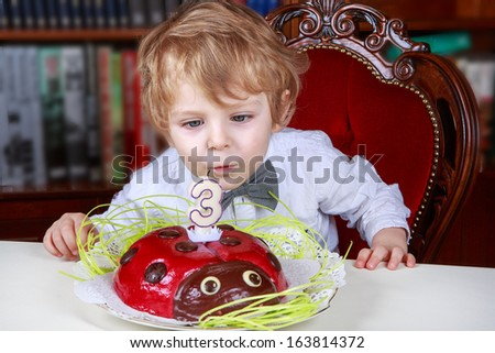 Cute three year old boy celebrating his birthday and blowing off the candles on the cake - stock photo