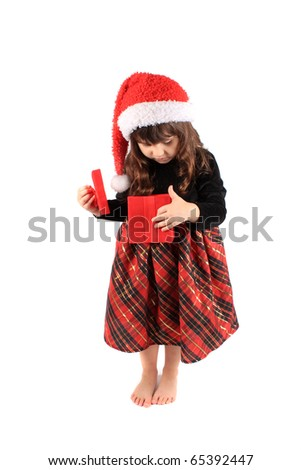 Cute three year old little girl dressed up in a fancy dress and christmas hat holding and looking into a a red giftbox standing barefoot on a white background - stock photo