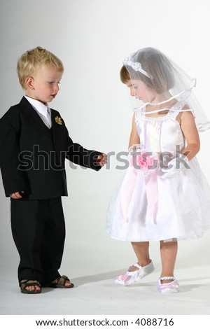 cute toddler boy and girl dressed like bride and groom the groom presenting a ring to the bride - stock photo