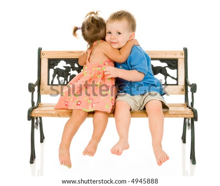 Cute toddler boy and girl in sundress embrace on a wooden and iron park bench. Isolated on white.