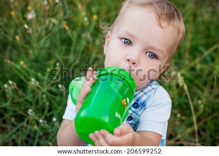 cute toddler boy drinking water outdoors - stock photo