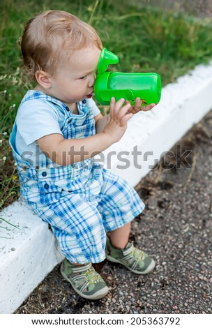 cute toddler boy drinking water sitting on the curb - stock photo