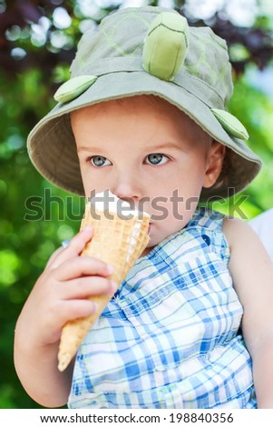 cute toddler boy eating ice cream on a summer day - stock photo