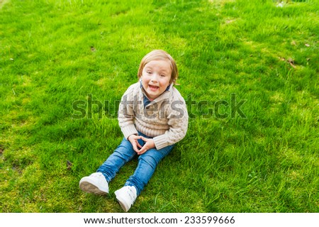 Cute toddler boy having fun outdoors on a nice sunny day in early spring - stock photo