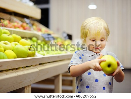 Cute toddler boy in a food store or a supermarket choosing fresh apples. Healthy lifestyle for young family with kids