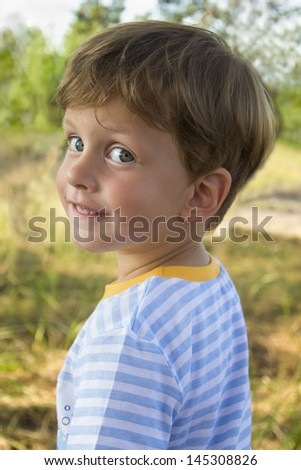 Cute toddler boy in summer forest