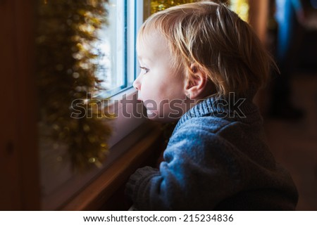 Cute toddler boy looking at the window at Christmas time - stock photo