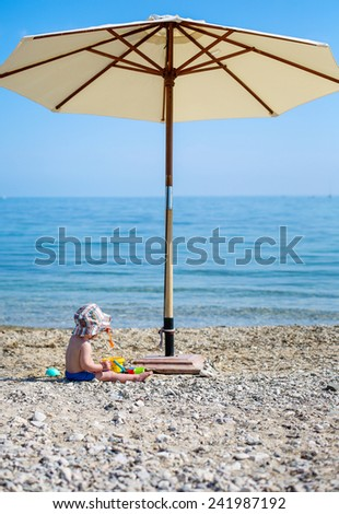 cute toddler boy playing on the beach under an umbrella - stock photo