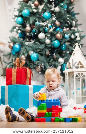 Cute toddler boy playing with building blocks at Christmas tree  - stock photo