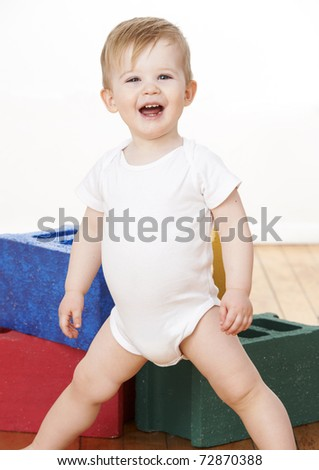 Cute toddler boy playing with colorful blocks on floor. - stock photo