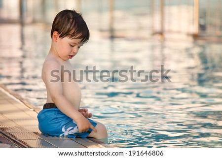 Cute toddler boy sitting by a swimming pool - stock photo
