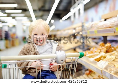 Cute toddler boy sitting in the shopping cart in a food store or a supermarket  - stock photo