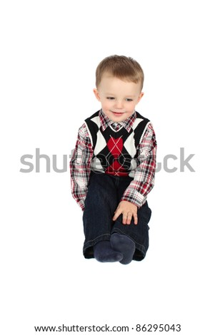 Cute toddler boy sitting on a white background
