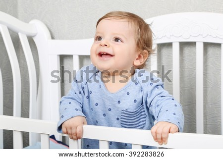 cute toddler boy standing in his crib