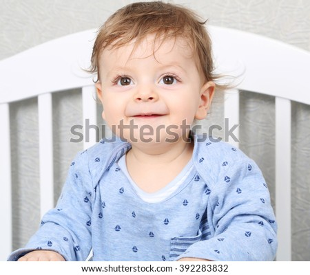 cute toddler boy standing in his crib - stock photo
