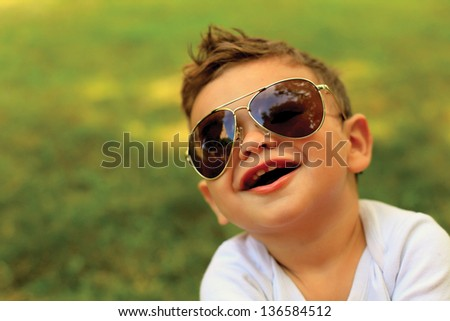 Cute toddler boy wearing sunglasses and looking at the camera - stock photo