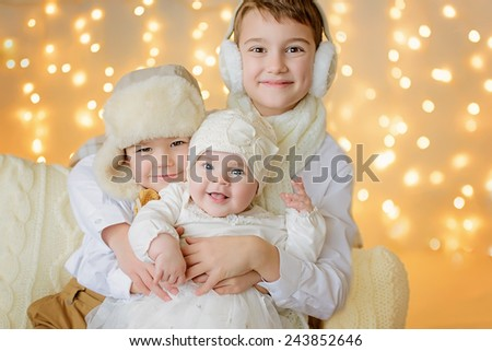 Cute toddler boys and little girl against warm soft Christmas lights