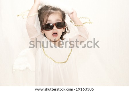 cute toddler girl dressed in angel costume wearing sunglasses taking off her halo against white background - stock photo