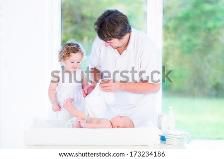 Cute toddler girl helping her father to change a diaper of her newborn baby brother - stock photo
