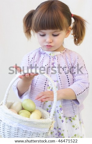 Cute toddler girl holding a basket of Ester eggs - stock photo