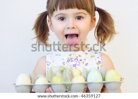 Cute toddler girl holding a carton of Easter eggs and making faces - stock photo