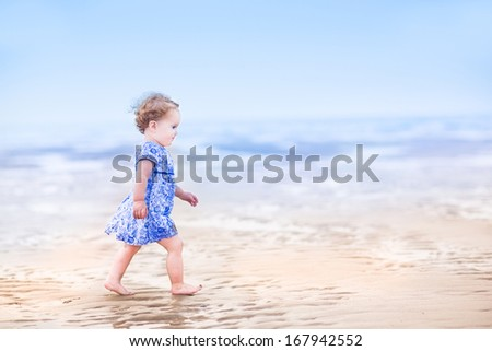 Cute toddler girl in a blue dress walking on a beach at sunset - stock photo