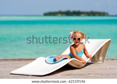 cute toddler girl in bikini and sunglasses lying on a lounge and relaxing in tropic ocean background - stock photo