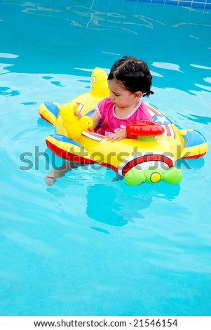 cute toddler girl in plane inflatable toy in swimming pool - stock photo