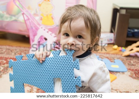 Cute toddler girl playing in child room, Colorful numbers 1, 2, 3, in a row of flat foam number toys