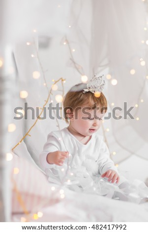 Cute toddler girl playing on a bed between warm soft Christmas lights