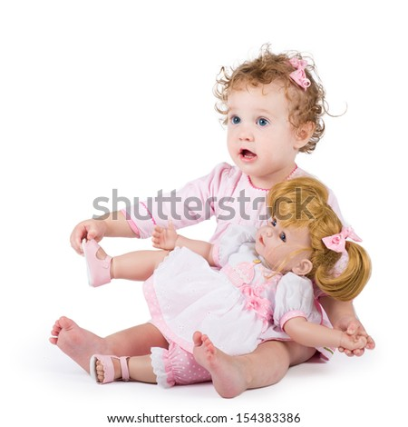 Cute toddler girl playing with her first doll - stock photo